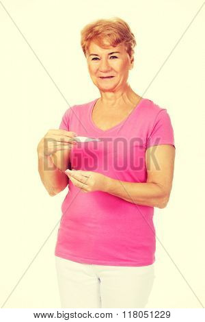 Smiling senior woman holding thermometer