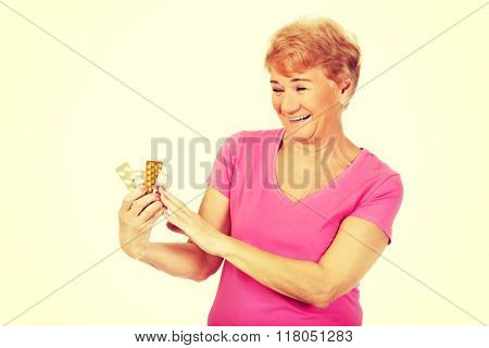 Smiling senior woman holding few tablets package