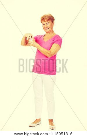 Smiling senior woman holding jar of pills