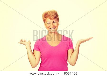 An old smiling woman presenting something