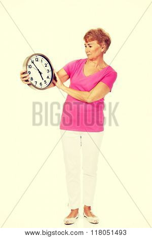 Worried senior woman holding big clock