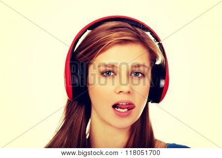 Teenage woman listens to music and shows tounge