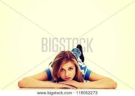 Pensive teenage woman lying on the floor