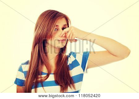 Teenage woman holding her nose because of a bad smell