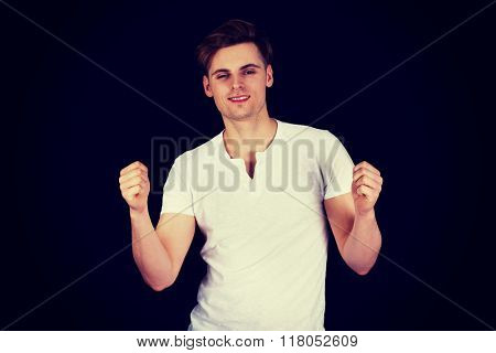 Young man showing winner gesture.