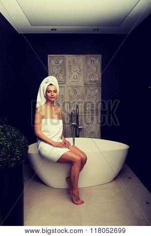 Beautiful woman sitting on bathtub.