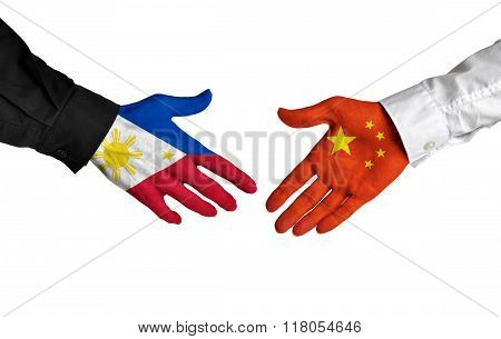 Philippines and China leaders shaking hands on a deal agreement