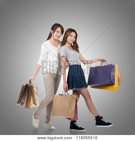 Happy smiling shopping girls of Asian holding bags with her friends.