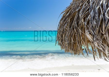 Beach Umbrella made of palm leafs on exotic beach