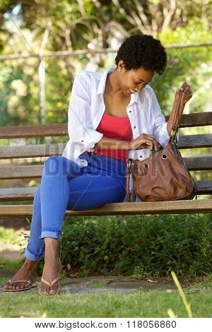 Young African Woman Sitting On A Park Bench With A Bag
