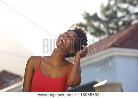 Young Black Woman Laughing Outdoors With Her Hand In Hair