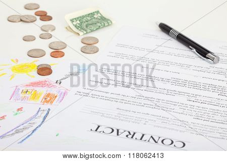 Contract of house sale or mortgage papers with a piggy and money