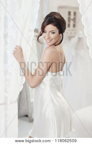 Beautiful young woman wearing slip made of silk, smiling happy.
