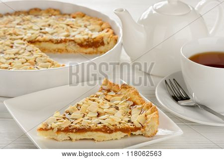 Piece of pie with carmel and almond. and cup of tea.