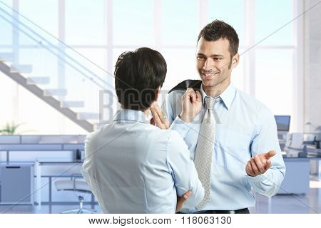 Young happy caucasian businessman talking to colleague at business office. Smiling, pointing, suit, jacket on back, standing. Copyspace.