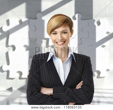 Attractive happy caucasian blonde female business office worker. Portrait, toothy smile, standing, looking at camera, arms crossed, woman suit, jigsaw puzzle background.