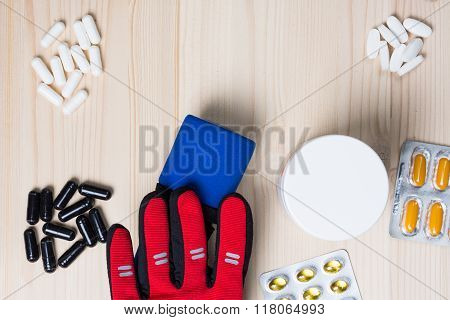 Sport supplements, a barbell and a sport glove on a wooden background