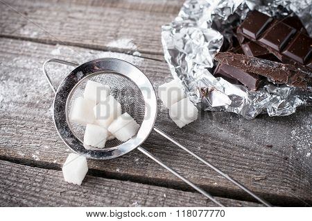 Lump Sugar In A Metal Strainer And Black  Dark Chocolate Pieces On Wooden Background. Ingredient For
