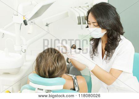 Closeup of dentist examining young woman's teeth