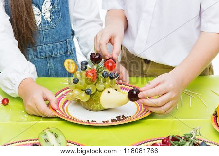 Children making fruit hedgehog