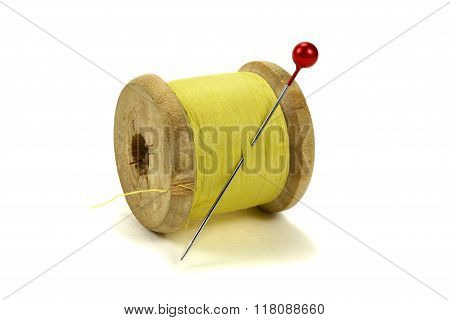 Wooden Coil With Threads And Pin For Sewing On A White Background