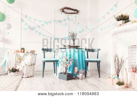 Beautiful Easter basket full of eggs on blue festive table in decorated room