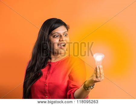 indian pretty lady holding glowing light bulb in hand, creativity concept, science concept, idea cli