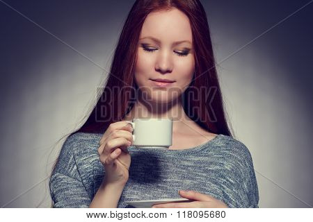 Beautiful young woman with a cup of coffee .