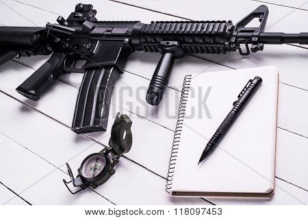 Notebook,pen,rifle And Compass On Wooden Table