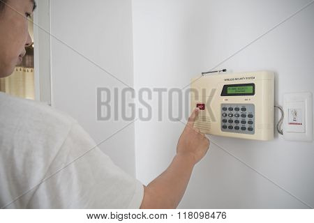 A guy pushing red button on home security system