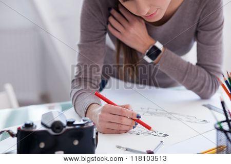Beautiful female photo artist is working in office
