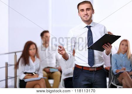 Smiling young businessman with paper holder and pen standing in front of colleagues