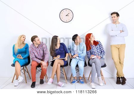 Young people sitting on a chairs and looking at the man in white hall