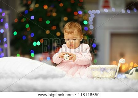 Sweet baby girl with jingle bell on Christmas background
