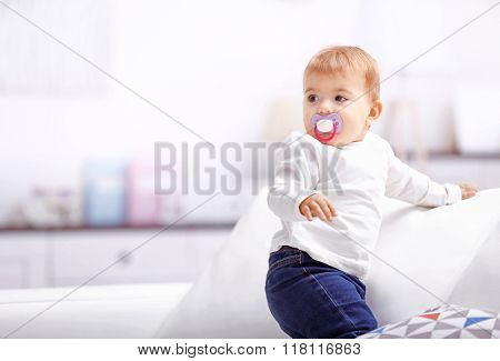 Sweet baby girl with a soother standing on sofa