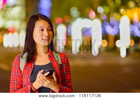 Close up portrait of woman with smartphone blured night city background