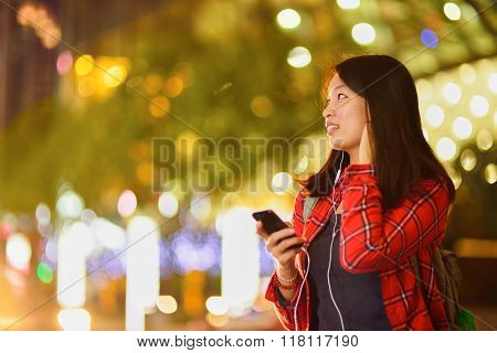 Close up portrait of woman listening music agains blured night city background