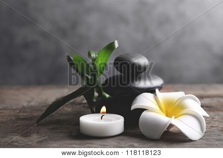Spa stones with candle, bamboo and tropical flower on wooden table against grey background