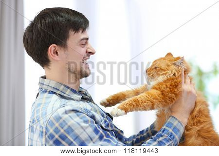 Angry young man holding a fluffy rad cat