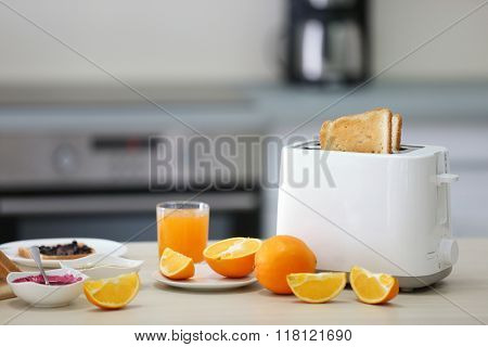 Toaster with dishes, sandwiches and oranges on a light kitchen table
