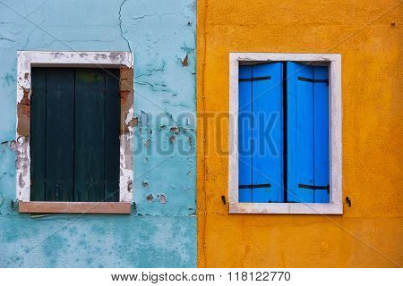 Old Walls Of Blue And Orange With The Windows Closed Shutters, Burano, Venice