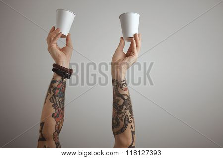 Two Tattooed Hands Hold Paper Glass In Air