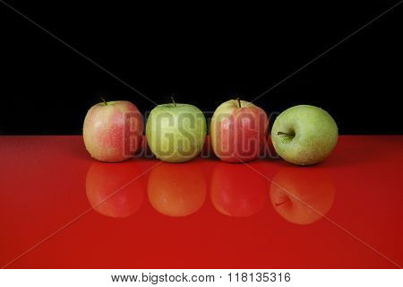 Fresh Green And Pink Apples On Red Table Top And Black Background, Copy Space