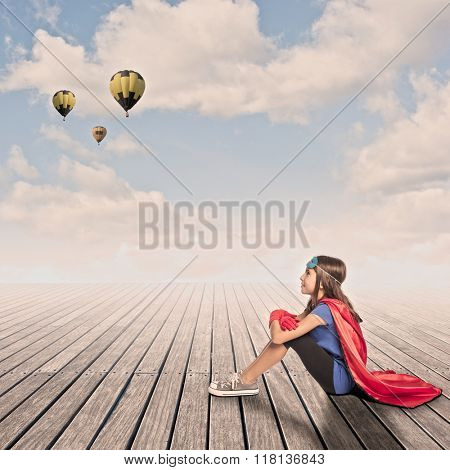 little girl wearing a superhero costume sitting on a wharf