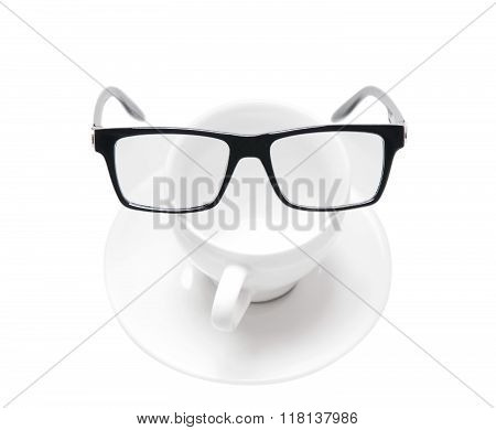 Black rimmed glasses on an empty coffee Cup