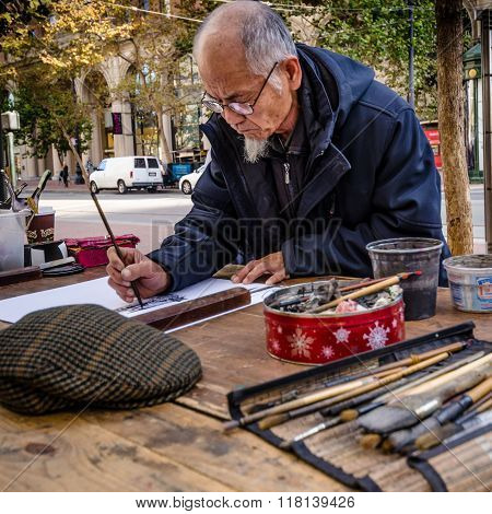 Asian Artist paints at a table on Market Street in San Francisco