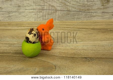 Easter Bunny And Egg Quail In The Stand On Wooden Background