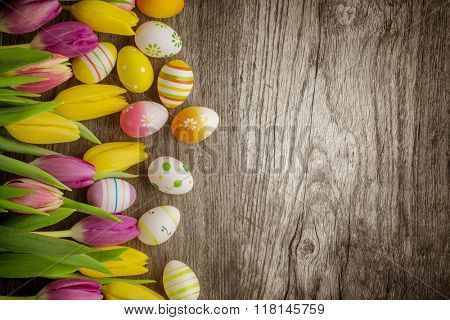 Tulips and easter eggs on rustic wood background