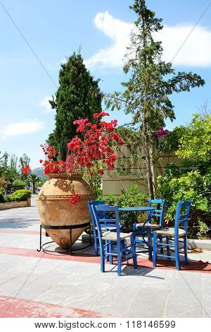 The Amphora With Flowers And Traditional Greek Table And Chairs At Luxury Hotel, Crete, Greece