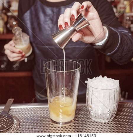Female bartender is adding an ingredient to the glass, toned